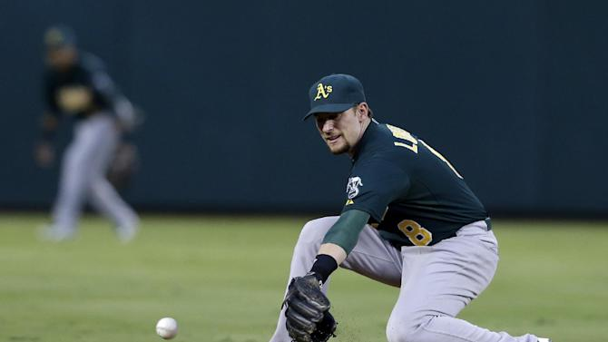 Oakland Athletics shortstop Jed Lowrie  commits an error  on a ground ball hit by Texas Rangers' David Murphy  in the fourth inning of a baseball game Tuesday, June 18, 2013, in Arlington, Texas. (AP Photo/Tony Gutierrez)