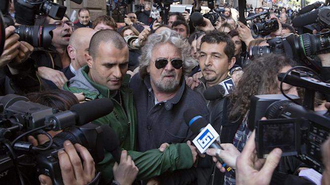 """This March 4, 2013 photo shows comic-turned-politician Beppe Grillo, at center with sunglasses, being surrounded by media as he leaves a hotel after a meeting with the elected members of his Movimento 5 Stelle movement, in Rome. These are crazy days in Rome - where limbo reigns in parliament and papacy. Italy is usually a pretty anarchic place, with people bucking rules on everything from crossing the street to paying taxes. But the anarchy's going a bit far: Who's running the country? Who's running the church? Nobody really knows. We Romans are living truly surreal times when a bearded comedian whose surname means """"cricket"""" is now one of the nation's most powerful leaders, and aging cardinals from around the world are mobbed by paparazzi as if they were Hollywood starlets.   (AP Photo/Roberto Monaldo, Lapresse) ITALY OUT"""