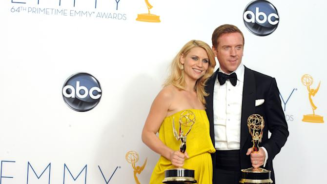 """FILE - This Sept. 23, 2012 photo shows actress Claire Danes, winner of the Emmy for Outstanding Lead Actress In A Drama Series for """"Homeland"""" and Actor Damian Lewis, winner Outstanding Lead Actor In A Drama Series for """"Homeland"""" posing backstage at the 64th Primetime Emmy Awards at the Nokia Theatre in Los Angeles. The second season of the Emmy award-winning series premieres Sunday at 10p.m. EST on Showtime. (Photo by Jordan Strauss/Invision/AP)"""