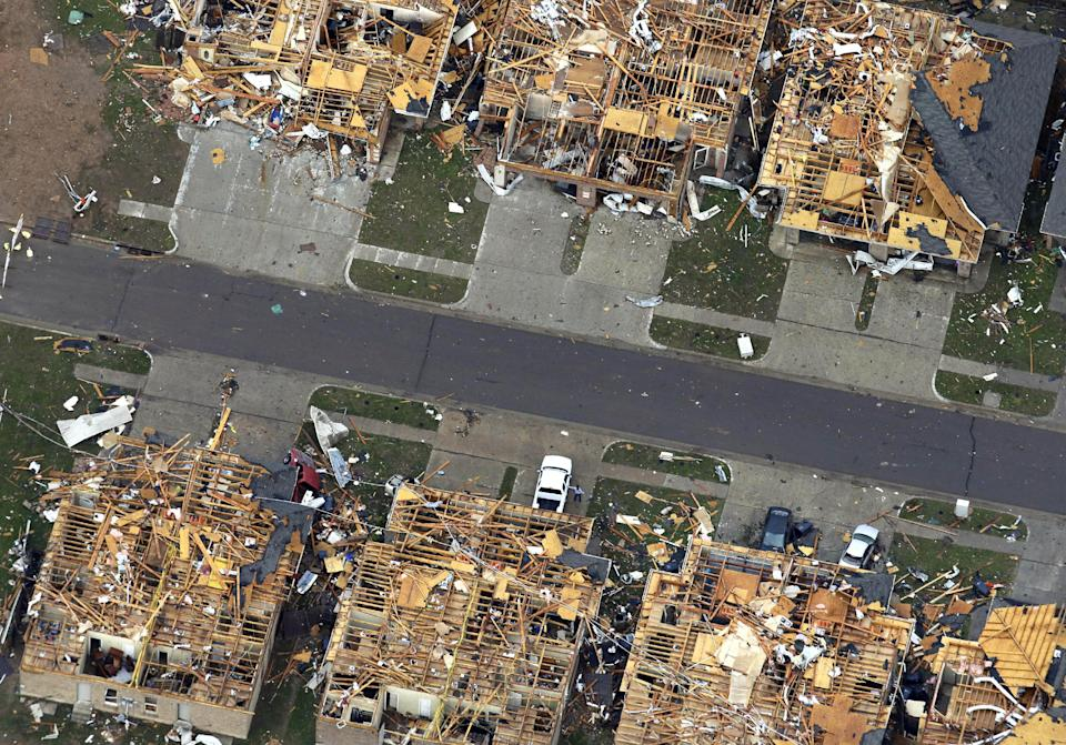 This Tuesday, May 21, 2013 aerial photo shows homes damaged by Monday's tornado in Moore, Oklahoma. The huge tornado roared through the Oklahoma City suburb, flattening entire neighborhoods and destroying an elementary school with a direct blow as children and teachers huddled against winds. (AP Photo/Tony Gutierrez)