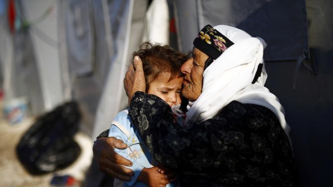 A Kurdish refugee woman from the Syrian town of Kobani hugs a child outside her tent in a camp in the southeastern town of Suruc