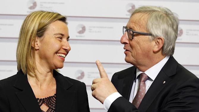 European Commission President Jean-Claude Juncker, right, gestures while speaking with European Union High Representative Federica Mogherini during arrivals at the Eastern Partnership summit in Riga, on Friday, May 22, 2015. EU leaders gather for a second day of meetings with six post-communist nations to discuss various issues, including enlargement, the economy and Ukraine. (AP Photo/Mindaugas Kulbis)