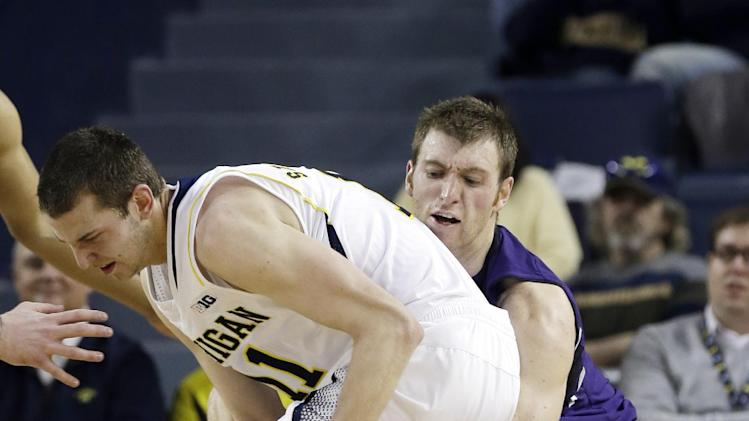 Northwestern guard Alex Marcotullio, right, reaches in on Michigan guard Nik Stauskas (11) during the first half of an NCAA college basketball game in Ann Arbor, Mich., Wednesday, Jan. 30, 2013. (AP Photo/Carlos Osorio)
