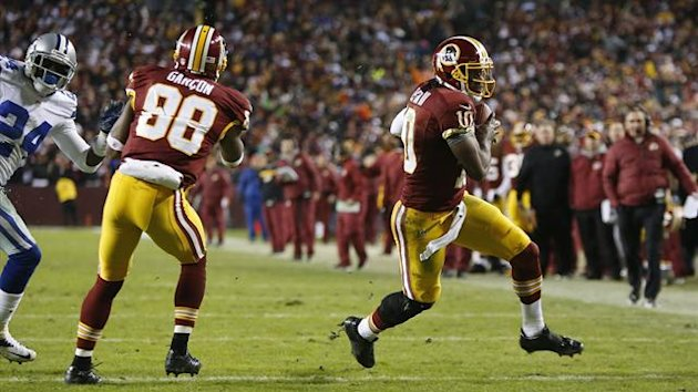 Washington Redskins quarterback Robert Griffin III (right) scores on a touchdown run during the second half of their NFL football game against the Dallas Cowboys