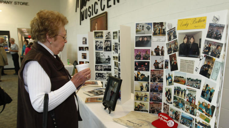Everly Brothers fan Ura Mae Jarvis, of Central City, Ky, look over memorabilia and photo's of The Everly Brothers before a memorial service for Phil Everly at the Merle Travis Music Center in Powderly, Kentucky, Saturday, Jan. 18, 2014. (AP Photo/John Sommers II)