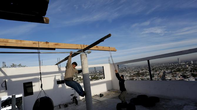 Residents prepare to hang a punching bag at the rooftop of an apartment as part of the Barrio Esperanza (Hope neighbourhood) project at the rough Cerro de la Campana neighbourhood in Monterrey
