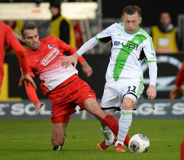 Freiburg's  Pavel Krmas , left, challenges for the ball with Wolfsburg's  Ivica Olic, during the German first division Bundesliga soccer match between SC Freiburg and VfL Wolfsburg in Freiburg