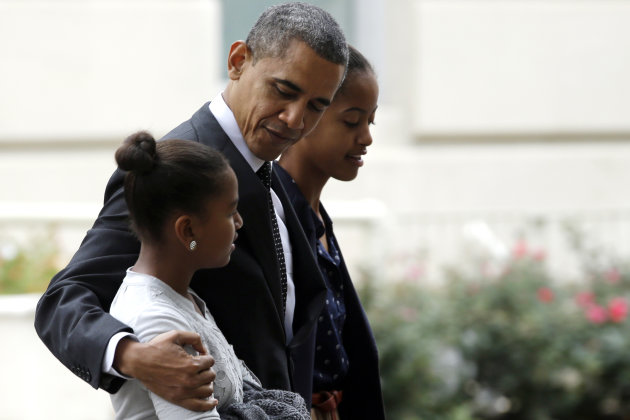 President Barack Obama hugs his daughter Sasha as he walks with Malia as they leave St. John's Episcopal Church to walk across Lafayette Park as they return to the White House in Washington, on Sunday