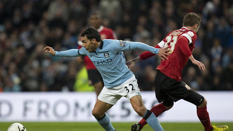 Manchester City's Carlos Tevez keeps the ball from Barnsley's Tom Kennedy during their English FA Cup quarterfinal soccer match at The City of Manchester Stadium, Manchester, England, Saturday, March 9, 2013. (AP Photo/Jon Super)