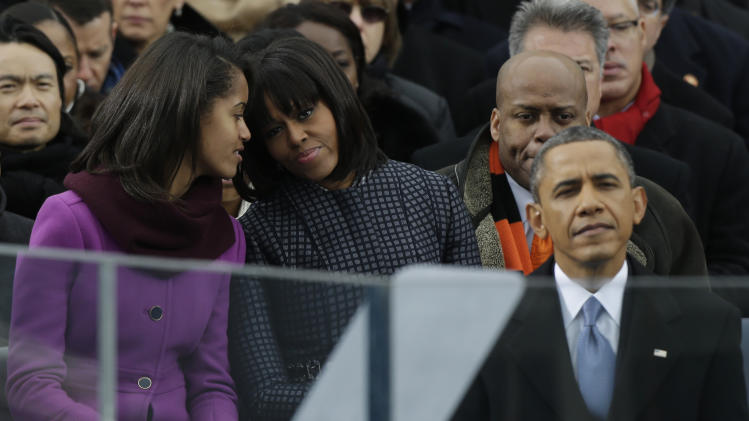 First lady Michelle Obama listens to her daughter Sasha at the ceremonial swearing-in for President Barack Obama at the U.S. Capitol during the 57th Presidential Inauguration in Washington, Monday, Jan. 21, 2013. (AP Photo/Pablo Martinez Monsivais)