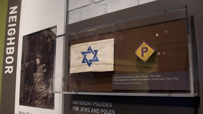 """This Thursday, April 25, 2013 photo shows an armband with the Star of David and a badge for a forced laborer in Germany at the United States Holocaust Memorial Museum during a preview of the new exhibit """"Some Were Neighbors: Collaboration & Complicity in the Holocaust"""" in Washington. The exhibition, opening April 30, 2013, includes interviews with perpetrators of collaboration and complicity in the Nazi genocide. (AP Photo/Carolyn Kaster)"""