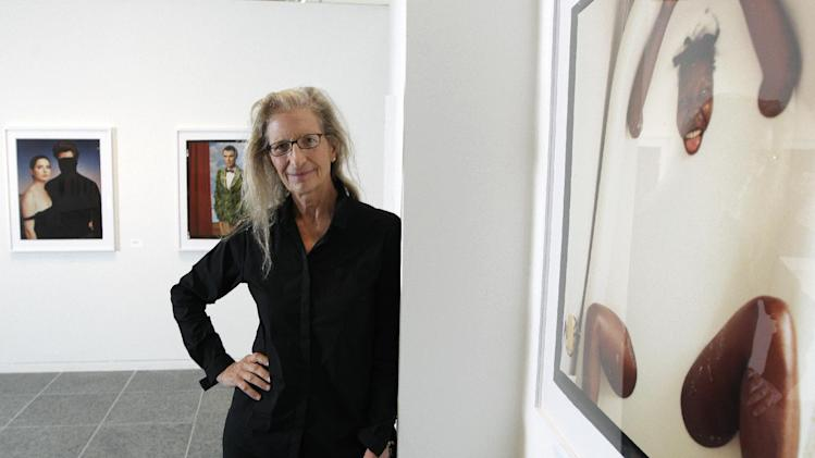 "Annie Leibovitz stands near some of her work before the opening of her exhibition at the Wexner Center for the Arts Friday, Sept. 21, 2012, in Columbus, Ohio. Leibovitz's exhibition features work from her ""Master Set,"" an authoritative edition of 156 images. (AP Photo/Jay LaPrete)"