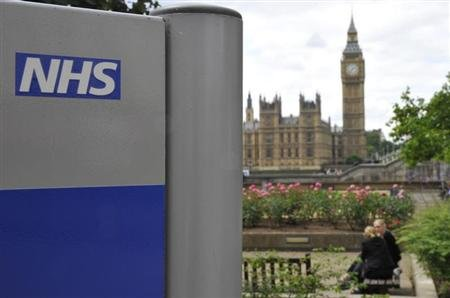 A National Health Service (NHS) sign is seen in the grounds of St Thomas&#39; Hospital, in front of the Houses of Parliament in London June 7, 2011. REUTERS/Toby Melville