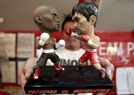 Store employee holds up a stand with miniature figurines of boxers Pacquiao of the Philippines and Mayweather Jr. of the U.S., at a mall in Manila