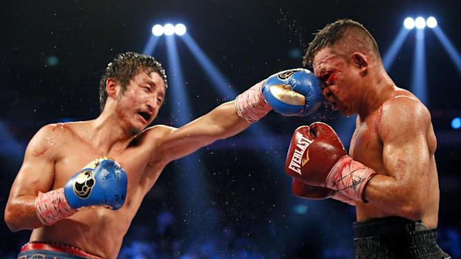 FILE - This July 19, 2014, file photo shows Chinese boxer Zou Shiming, left, delivering a punch to Colombian boxer Luis De La Rosa during the WBO international flyweight title match in Macau, China. China's double Olympic gold medalist goes after the IBF's 112-pound belt against Thailand's tough Amnat Ruenroeng in Macau this weekend, eager to justify his enormous popularity with a world title in just his seventh pro fight. (AP Photo/Dennis Ho, File)