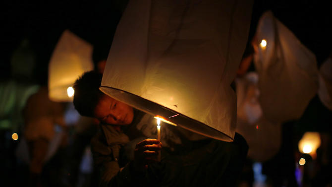 A Thai man lights a lantern before releasing it to symbolize the releasing of spirits of victims of the Asian tsunami during a commemoration service to mark the 10th anniversary of the day this natural disaster happened, Friday, Dec. 26, 2014 in Ban Nam Khem, Thailand. Dec. 26 marks the 10th anniversary of one of the deadliest natural disasters in world history: a tsunami, triggered by a massive earthquake off the Indonesian coast, that left more than 230,000 people dead in 14 countries and caused about $10 billion in damage. (AP Photo/Wong Maye-E)