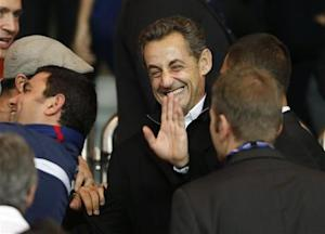 Former French President Sarkozy waves as he arrives to attend the Paris St Germain and Monaco French Ligue 1 soccer match at the Parc des Princes Stadium in Paris