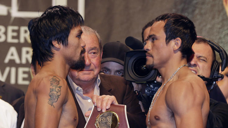 Manny Pacquiao, left, and Juan Manuel Marquez pose for photos after the weigh-in for their welterweight fight, Friday, Dec. 7, 2012, in Las Vegas. The pair face off in the fourth fight against each other on Saturday. (AP Photo/Julie Jacobson)