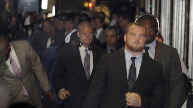 Dallas Cowboys football players and support staff get off the team bus as they arrive at their hotel, Saturday Dec. 8, 2012, in Cincinnati, for Sunday's NFL football game against the Cincinnati Bengals. Cowboys practice-squad player Jerry Brown was killed in a one-car accident Saturday in Irving, Texas, and teammate Josh Brent was charged with intoxication manslaughter.(AP Photo/Tom Uhlman)
