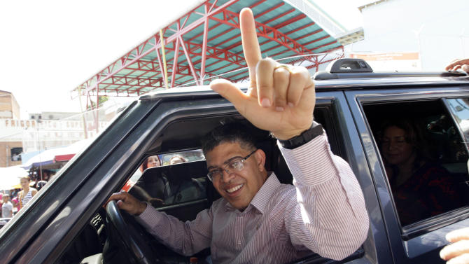 Elias Jaua, Venezuela's former Vice President and candidate for governor of Miranda state, gestures from the inside of a vehicle as he leaves after casting his ballot at a polling station in Caracas, Venezuela, Sunday, Dec. 16, 2012. Venezuelans are choosing governors and state lawmakers in elections that have become a key test of whether President Hugo Chavez's movement can endure if the leader leaves the political stage. (AP Photo/Ariana Cubillos)