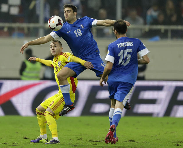 Greece's Sokratis Papstathopoulos (19) jumps for the ball with Romania's Alexandru Iulian Maxim during their World Cup qualifying playoff first leg soccer match at the Karaiskaki stadium in the port o