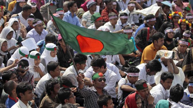 FILE - In this Wednesday, Feb. 13, 2013 file photo, Bangladeshi activists participate in a rally demanding the execution of Jamaat-e-Islami leader Abdul Quader Mollah and others convicted of war crimes in Dhaka, Bangladesh. For many in Bangladesh, the ''V'' for victory sign was more than they could bear. They had waited more than four decades for justice in the mass killings and rapes during their independence war. But there was a smiling Mollah apparently celebrating his life sentence - given in place of an expected death sentence - for his role in the killing of 381 civilians. Within hours, thousands of university students demanding his death poured into the streets of Dhaka, the seeds of what has grown into a mass protest that has exposed again the unhealed wounds from the nation's 1971 war for independence from Pakistan. (AP Photo/A.M. Ahad, File)