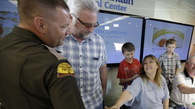 Lynette Hales shakes hands with Utah Trooper Cameron Fawson while Jim Gerber, center, watches following a news conference at Intermountain Medical Center Monday, June 3, 2013, in Murray, Utah. Hales was nearly 100 miles from Salt Lake City on a rural stretch of highway surrounded by nothing but barren salt flats when her twin unborn babies decided it was time. She called police for help, but the nearest highway troopers were about 30 miles east on Interstate 80. The first baby couldn't wait. She delivered him at about 9 a.m. Sunday from the passenger seat of a minivan with the help of a friend who was driving her back from an overnight outing in Wendover. Her twin boys, J.J. and A.J., were born in a minivan with the help of Gerber and Fawson along with two other law enforcement officers. (AP Photo/Rick Bowmer)