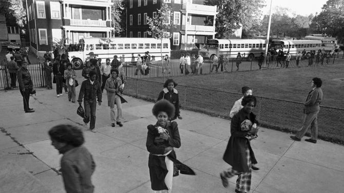 In this Oct. 18, 1974 file photo, school buses bringing students to Boston's Hyde Park High School arrive without incident. The nonprofit Union of Minority Neighborhoods is hosting group exercises across Boston in 2013, where participants talk about how the city's busing crisis impacted them in the 1970s. Organizers hope it will unite people to fight for better access to quality public schools for all students, even as another new Boston school assignment system starts. (AP Photo/J. Walter Green, File)