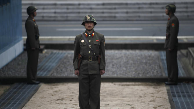 """North Korean soldiers stand guard in front of the truce village of Panmunjom at the Demilitarized Zone (DMZ) which separates the two Koreas seen from the North side, Monday, April 23, 2012. North Korea promised Monday to reduce South Korea's conservative government """"to ashes"""" in less than four minutes, in an unusually specific escalation of recent threats aimed at its southern rival. (AP Photo/Ng Han Guan)"""