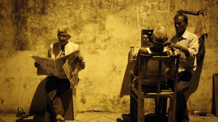A man gets his shave done by a roadside barber as another reads a newspaper while waiting for his turn, in New Delhi