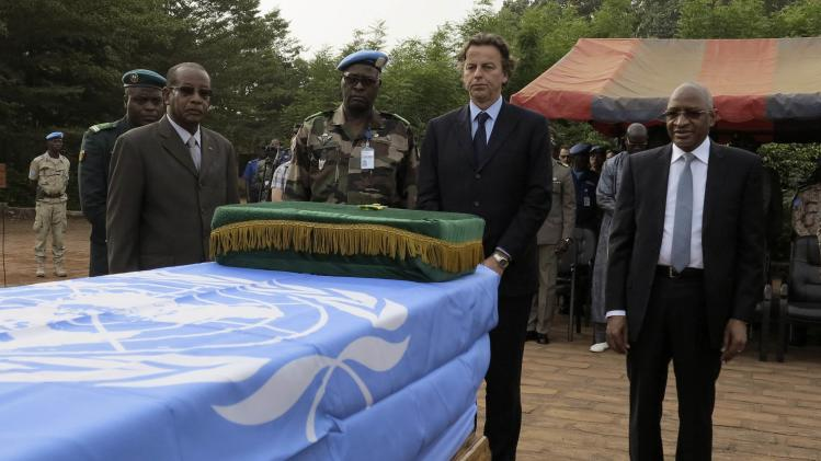 Koenders of MINUSMA and Malian Defense Minister Maiga pay their respects to U.N. soldiers during their funeral in Bamako