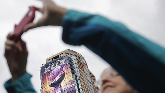 A banner of the Vince Lombardi Super Bowl Trophy decorates a building as fans take photos of the downtown festivities, Saturday, Jan. 31, 2015, in Phoenix. The New England Patriots face the Seattle Seahawks in Super Bowl XLIX on Sunday, Feb. 1, 2015, in Glendale, Ariz