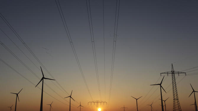 In this photo taken Oct. 12, 2012, the sun rises behind electricity poles and wind turbines  in Nauen, near Berlin, Germany. Germany's tax on households' electricity bills to finance the expansion of renewable energies will rise almost 50 percent on the year as the country pushes ahead with phasing out nuclear power within a decade. The country's four main grid operators say Monday Oct. 15, 2012 that the tax will rise from 3.6 euro cents to 5.3 euro cents (US $6.7 cents) per kilowatt hour starting in January. (AP Photo/Ferdinand Ostrop)