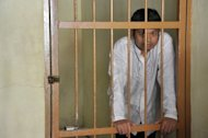 Thirty year old Indonesian, Alexander Aan waits in the jail holding area during his verdict at the Muaro Sijunjung district court in West Sumatra. Aan, who wrote &quot;God doesn&#39;t exist&quot; on his Facebook page, was jailed for 30 months for sharing explicit material about the Prophet Mohammed online
