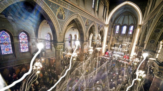 FILE - In this March 24, 2013 file photograph taken with a long exposure, Romanian Catholic worshipers attend a Palm Sunday religious service at the St. Joseph cathedral in Bucharest, Romania. Bucharest enjoys a rich multi-faith tradition, revived since 1989, with synagogues, mosques, and Romanian Orthodox churches in every neighborhood.  It was founded by a shepherd, according to local legend, and was later nicknamed the Paris of the East. But Bucharest's idyllic roots and elegant reputation eventually gave way to a series of 20th century calamities: war, invasions, earthquakes and communism.(AP Photo/Vadim Ghirda, File)