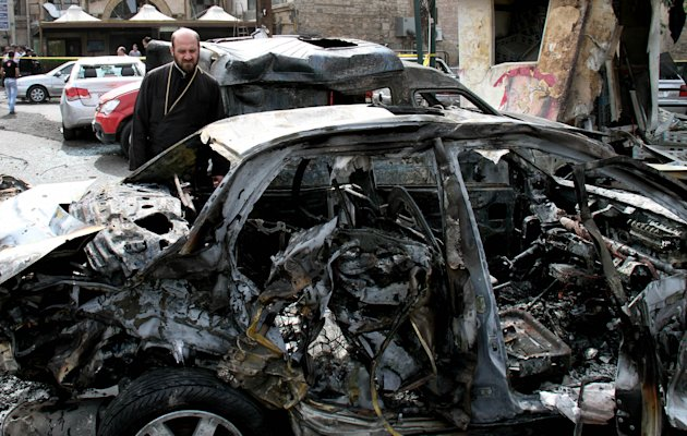 A Syrian man looks at a damaged cars at the site after a car bomb attack in Bab Touma neighborhood, a popular shopping district largely inhabited by Syria's Christian minority in Damascus, Syria, Sunday, Oct. 21, 2012. A taxi rigged with explosives blew up outside a police station in the Syrian capital Sunday, killing at least 13 people even as the U.N. envoy to the nation's crisis was visiting Damascus to push his call for a cease-fire in talks with President Bashar Assad. The SANA state news agency said tens of people were wounded. (AP Photo/Bassem Tellawi)
