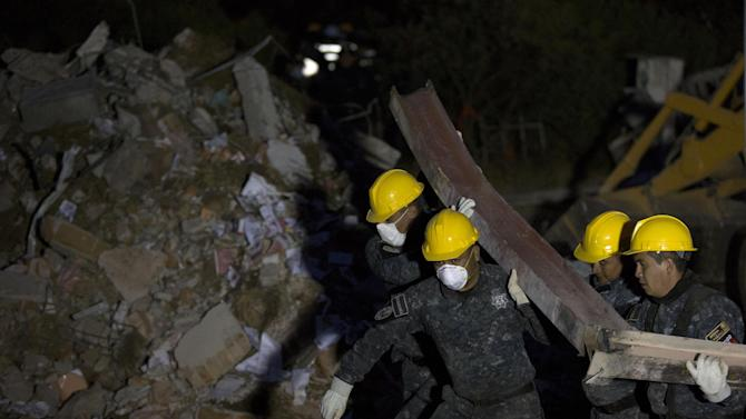 Rescue workers haul a bent beam from the rubble as the search for survivors continues into the night amongst the rubble of a maternity and children's hospital after a gas truck exploded in Cuajimalpa on the outskirts of Mexico City, Thursday, Jan. 29, 2015. The explosion, which collapsed the majority of the building, occurred in the morning when a tanker truck was making a routine delivery of gas to the hospital kitchen and gas started to leak. (AP Photo/Rebecca Blackwell)