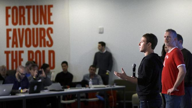 """Facebook CEO Mark Zuckerberg, second from right, speaks with Director of Engineering Lars Rasmussen at Facebook headquarters in Menlo Park, Calif., Tuesday, Jan. 15, 2013. Zuckerberg introduced """"graph search"""" Tuesday, a new service that lets users search their social connections for information about their friends' interests, and for photos and places.  (AP Photo/Jeff Chiu)"""