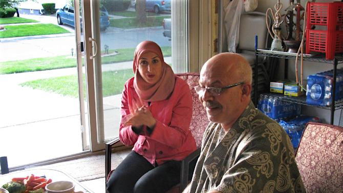 In this June 13, 2013 photo Mariam Khalaf, left, is seen with her Orchard Street neighbor, Muheeb Nabulsy in Dearborn, Mich. Both Khalaf and Nabulsy have added sliding doors to their garages and use them as patio-like spaces in addition to storage and are concerned about pending changes to Dearborn's ordinance related to garages. (AP Photo/Jeff Karoub)