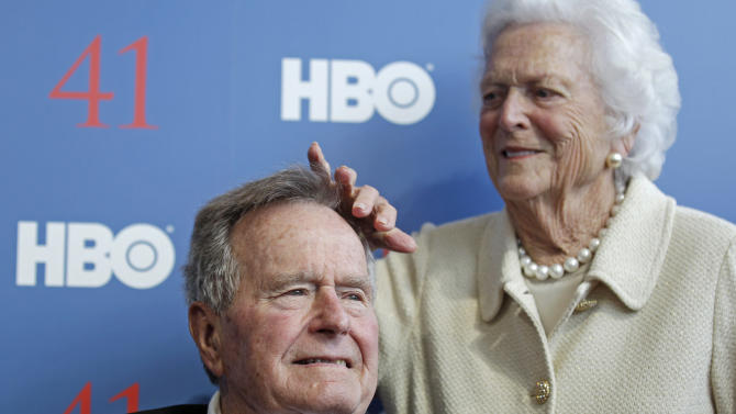 "Former first lady Barbara Bush touches the hair of her husband President George H.W. Bush as they arrive for the premiere of HBO's new documentary on his life in Kennebunkport, Maine, Tuesday, June 12, 2012.  The premiere of ""41"" was held Tuesday on Bush's 88th birthday on the grounds of St. Ann's Church in Kennebunkport, near the Bush family's summer home.(AP Photo/Charles Krupa)"