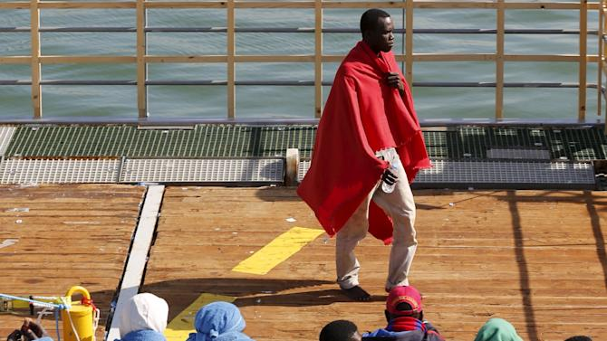 Migrants wait to disembark from the Norwegian vessel Siem Pilot at Catania's harbour