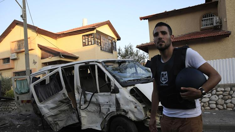 A man stands in front of a van damaged from a rocket fired from Gaza which landed in the middle of a residential neighborhood in the southern city of Kiryat Gat, Israel, Thursday, July 31, 2014. An Israeli was seriously wounded when a Palestinian rocket exploded in a residential area of the city. Another rocket was intercepted over Tel Aviv by Israel's rocket defense system. Israeli attacks on Gaza continued today, killing many people as Prime Minister Benjamin Netanyahu vowed to destroy the Hamas tunnel network. (AP Photo/Tsafrir Abayov)
