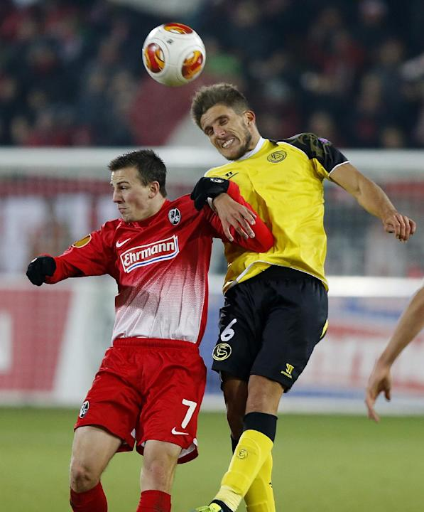 Freiburg's Vladimir Darida of Czech Republic, left, and Sevilla's Daniel Carrico challenge for the ball during a Group H Europa League match between SC Freiburg and Sevilla FC in Freiburg, Ger
