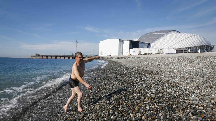 A man walks out of the sea after swimming during a sunny day as the Olympic Park is seen in the background, during the 2014 Winter Olympic Games in Sochi