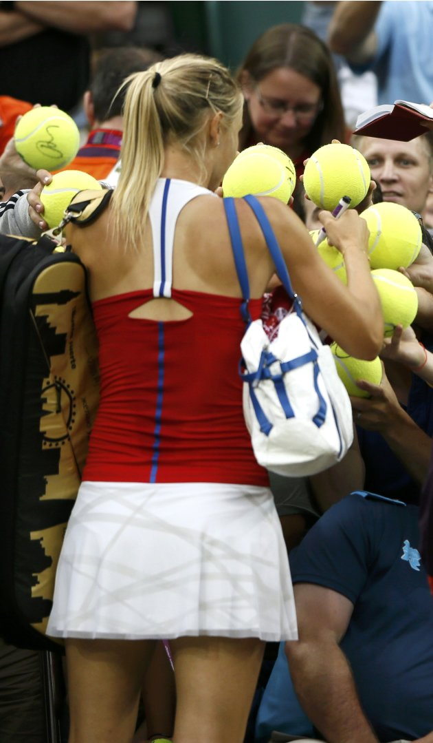 Russia's Sharapova signs autographs after winning against Israel's Peer in their women's singles tennis match at the All England Lawn Tennis Club during the London 2012 Olympics Games