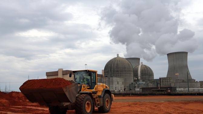 In this Tuesday, Dec. 11, 2012 photo, an earth mover works on a new nuclear reactor at the Plant Vogtle nuclear power plant in Augusta, Ga. One of the plant's existing reactors is shown in the background. The $14 billion project is trending hundreds of millions of dollars over budget and trailing more than a year behind schedule, according to a report from a state-hired construction watchdog. Buzz Miller, executive vice president of nuclear development at Southern Co., who oversees the project, says quality counts more than cost. (AP Photo/John Bazemore)