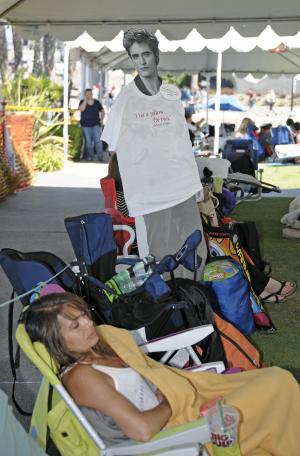 A woman sleeps in front of a Twilight cutout while in line during Preview Night at the Comic-Con 2011 convention, Wednesday, July 20, 2011 in San Diego.  Twilight fans have been waiting in line since Tuesday for the Twilight panel which will take place Thursday on the first day of Comic Con.   (AP Photo/Denis Poroy)