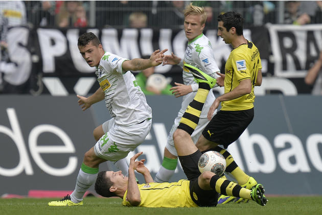 Moenchengladbach's Granit Xhaka of Switzerland, left, Dortmund's Robert Lewandowski of Poland, down, and Dortmund's Henrikh Mkhitaryan of Armenia, right, challenge for the ball during the German first