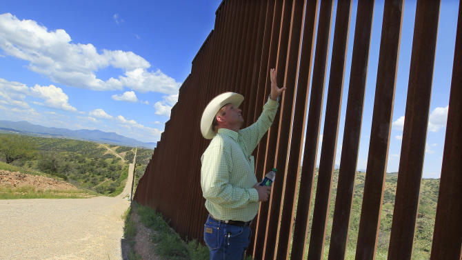 In this Friday, Aug. 10, 2012 photo, rancher Dan Bell checks out part of his property at the border fence between the United States and Mexico, in Nogales, Ariz. When Bell drives through his property, he speaks of the hurdles that the Border Patrol faces in his rolling green hills of oak and mesquite trees: The hours it takes to drive to some places, the wilderness areas that are generally off-limits to motorized vehicles, and the environmental reviews required to extend a dirt road. (AP Photo/Ross D. Franklin)