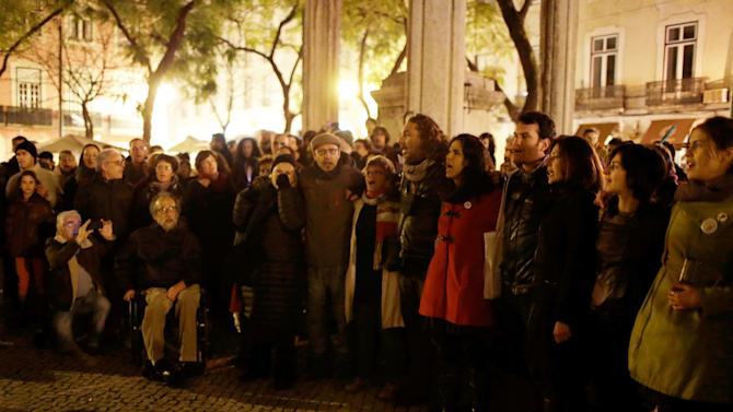"In this photo taken Feb. 23, 2013, people gather at Lisbon's Largo do Carmo square to sing ""Grandola, Vila Morena"" (Grandola, Dusky Town) to mark the 26th anniversary of the death of it's author, Zeca Afonso. A Portuguese revolutionary song from 40 years ago is haunting the bailed-out country's government. Anti-austerity protesters are hounding senior officials by loudly singing at public events a celebrated tune from the 1974 Carnation Revolution. They have managed to silence some of their targets, including the prime minister when he was trying to give a speech in Parliament. (AP Photo/Armando Franca)"